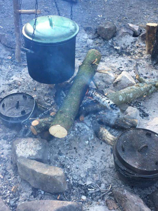 Töpfe über und in einem Lagerfeuer