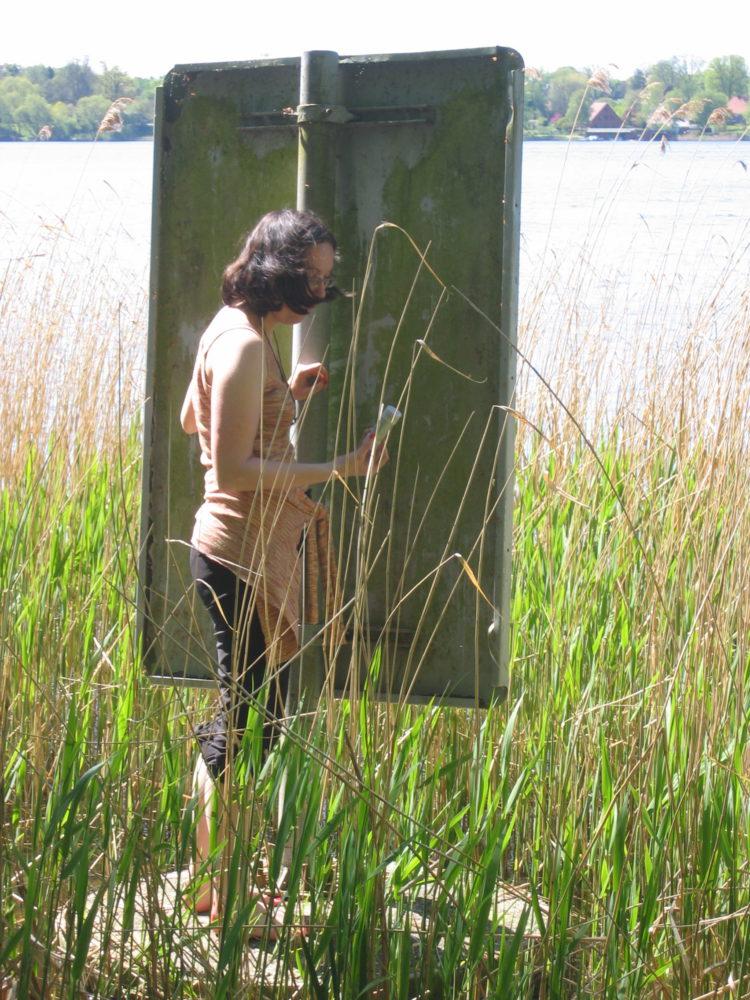 Beim Geocachen wir ein PET-Ling an einem Hinweisschild am Seeufer gefunden
