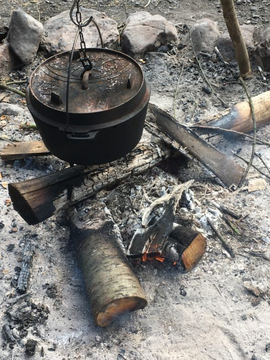 Ein Feuertopf, der über dem Lagerfeuer hängt